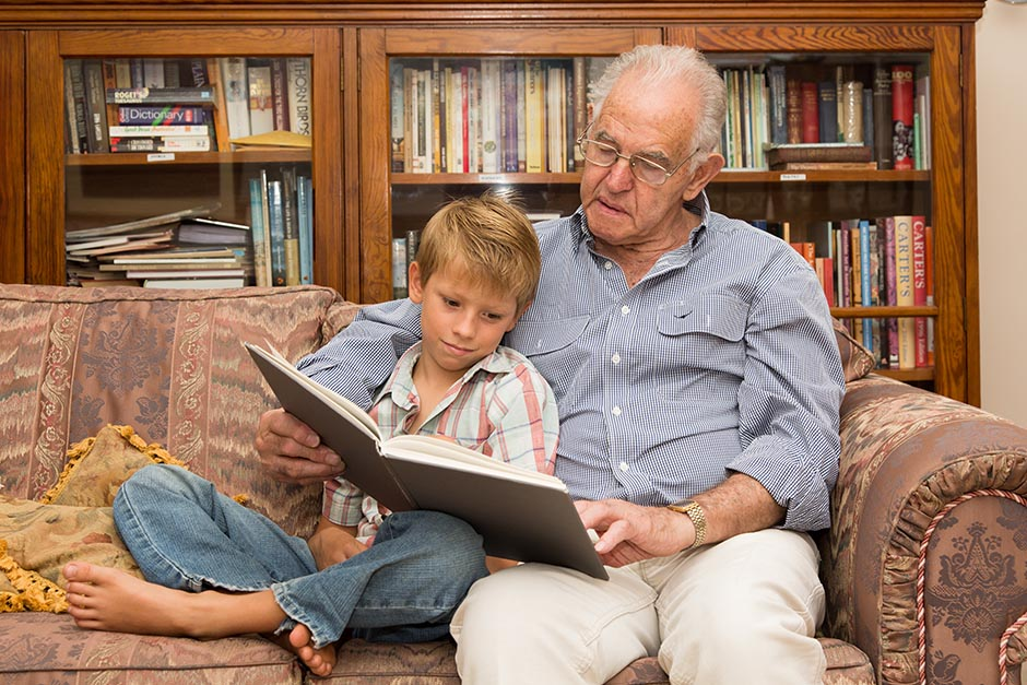 Photo of a child reading a book with his grandfather