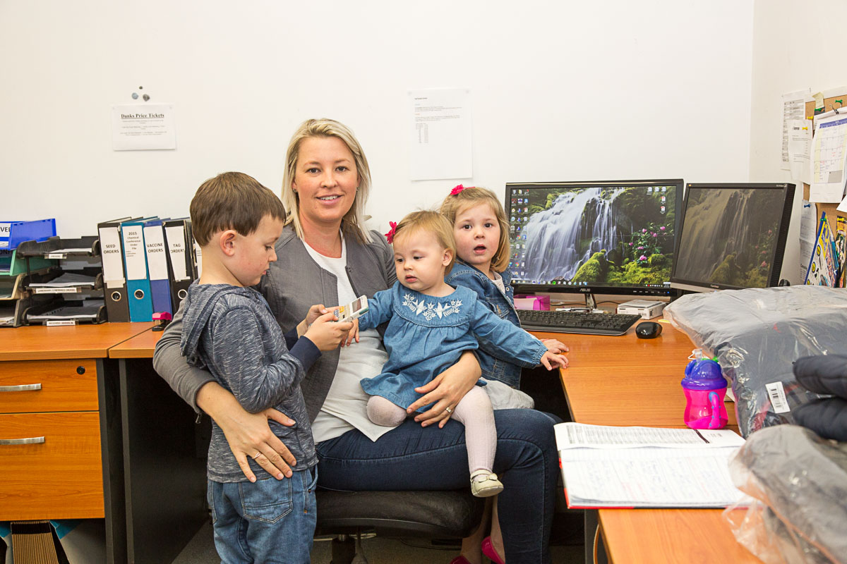 Photo of mother at office desk surrounded by her three young children. Photo by caro telfer, photographer.