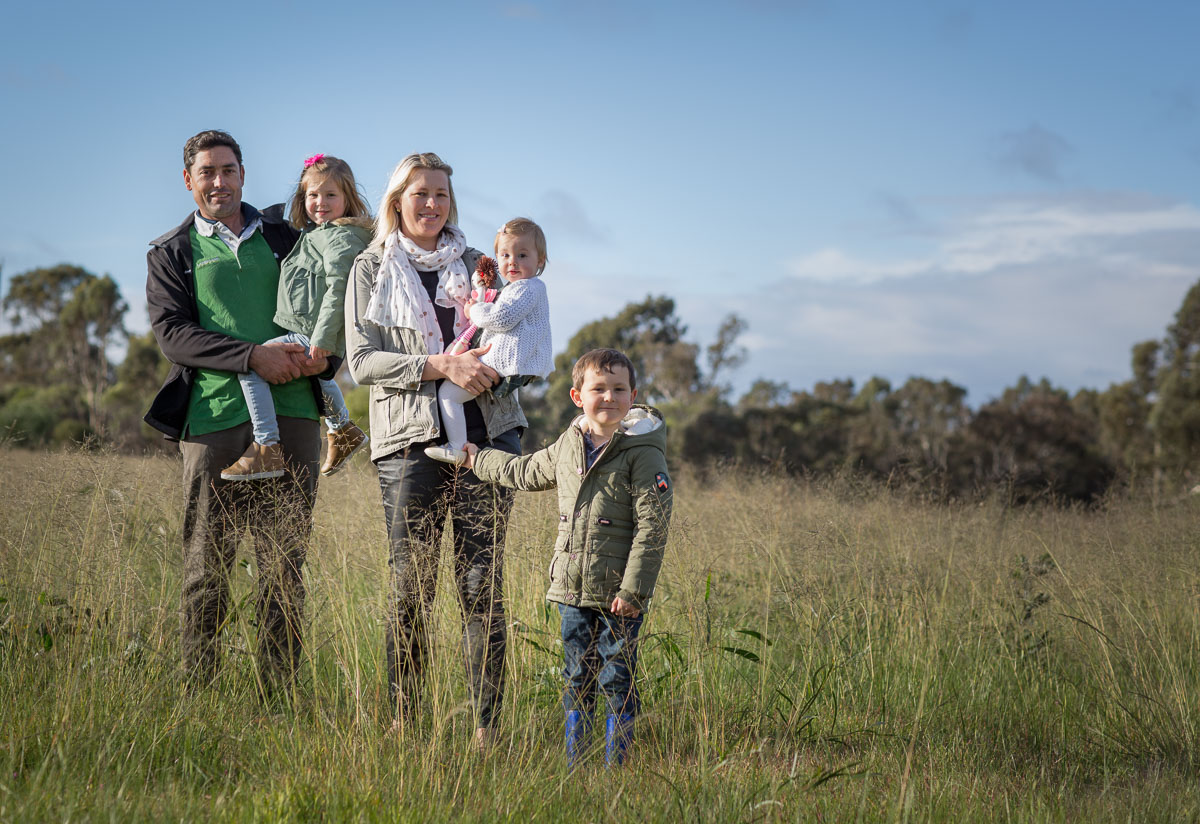 Photo off attractive young couple with their three children standing in a grassy field. Photo by Caro Telfer, photographer.