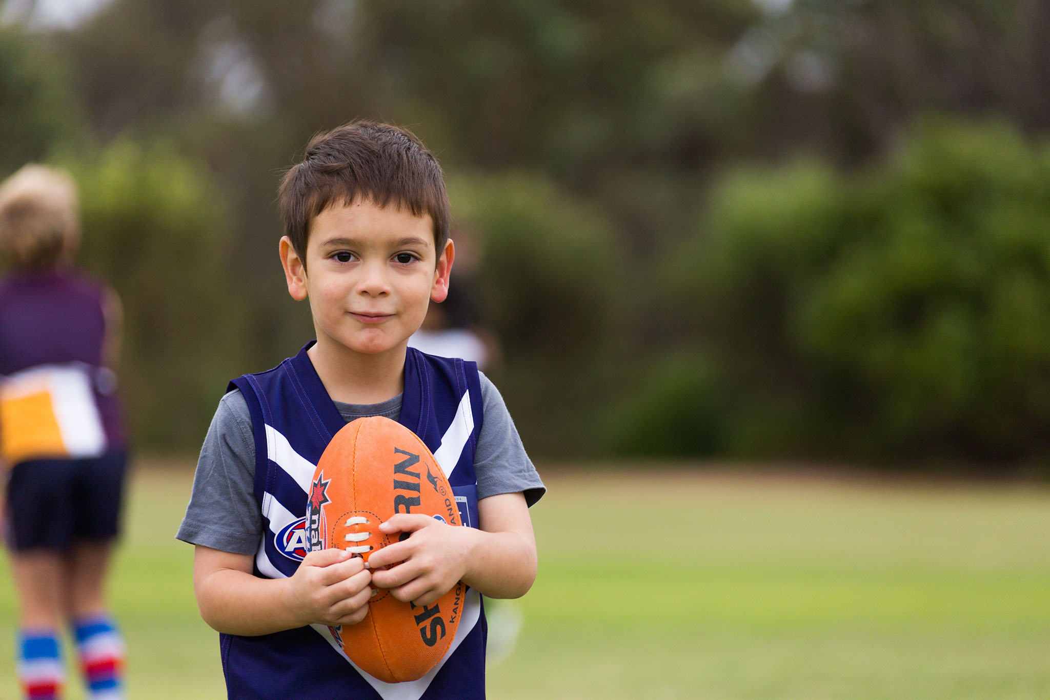 Photo of a young boy holding his football