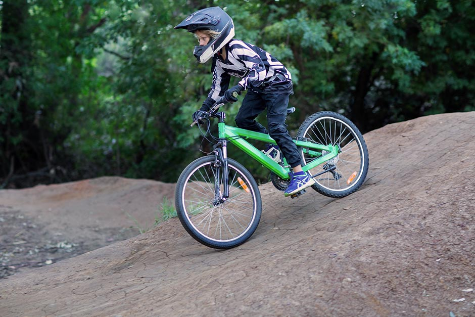photo of a kid wearing bike gear riding a pushbike