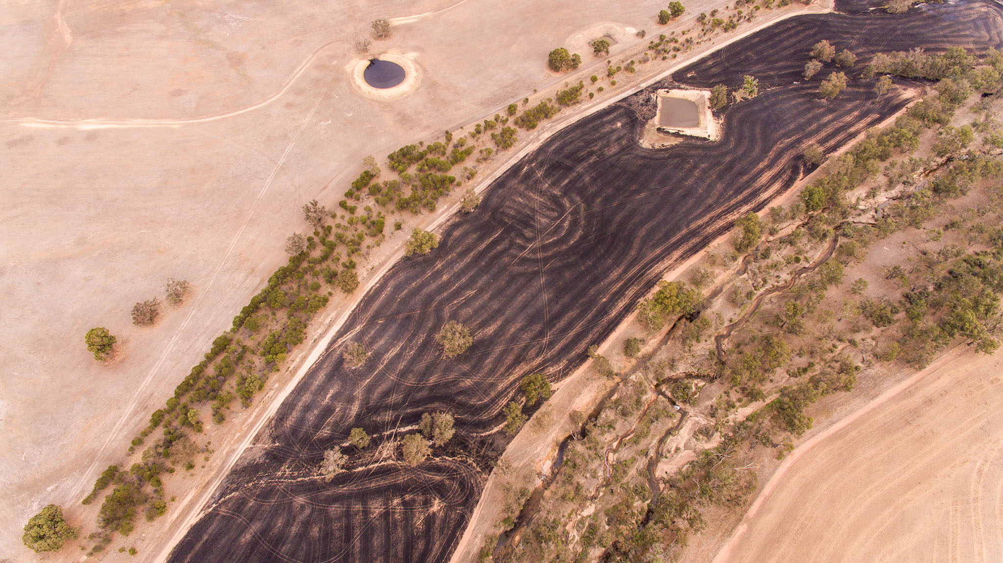 Aerial view of landscape with burnt black band arcing through the frame. Image by caro Telfer, Photographer.