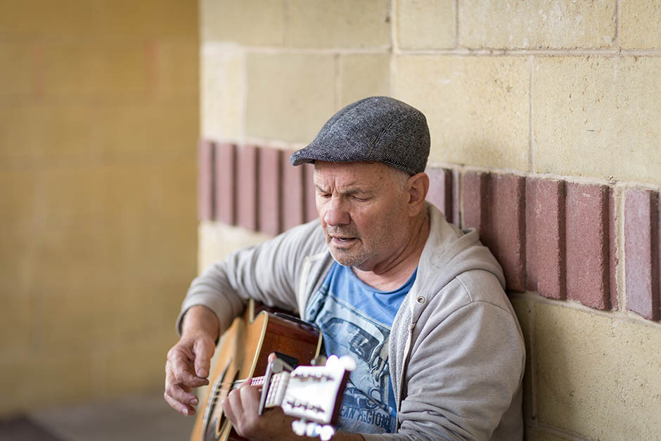 photo of a man playing a guitar, by caro telfer, photographer