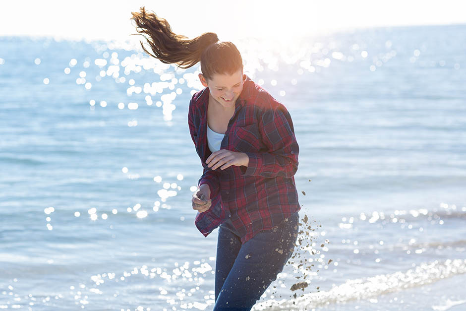 photo of teenage girl avoiding sand thrown at her on the beach. Photo by caro telfer.