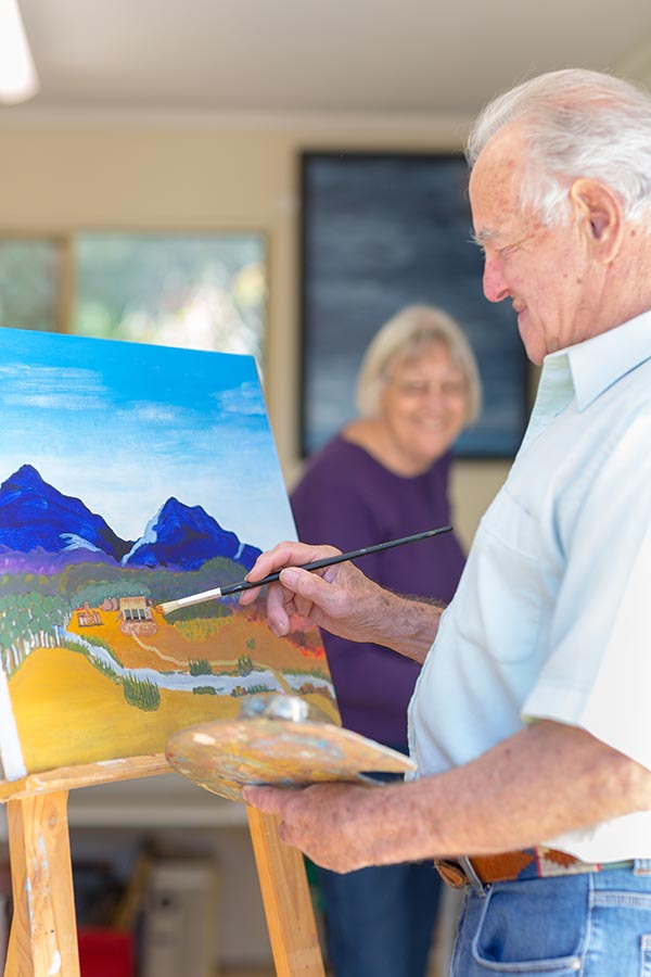 photo of an older couple painting in art studio. photo by Caro Telfer.