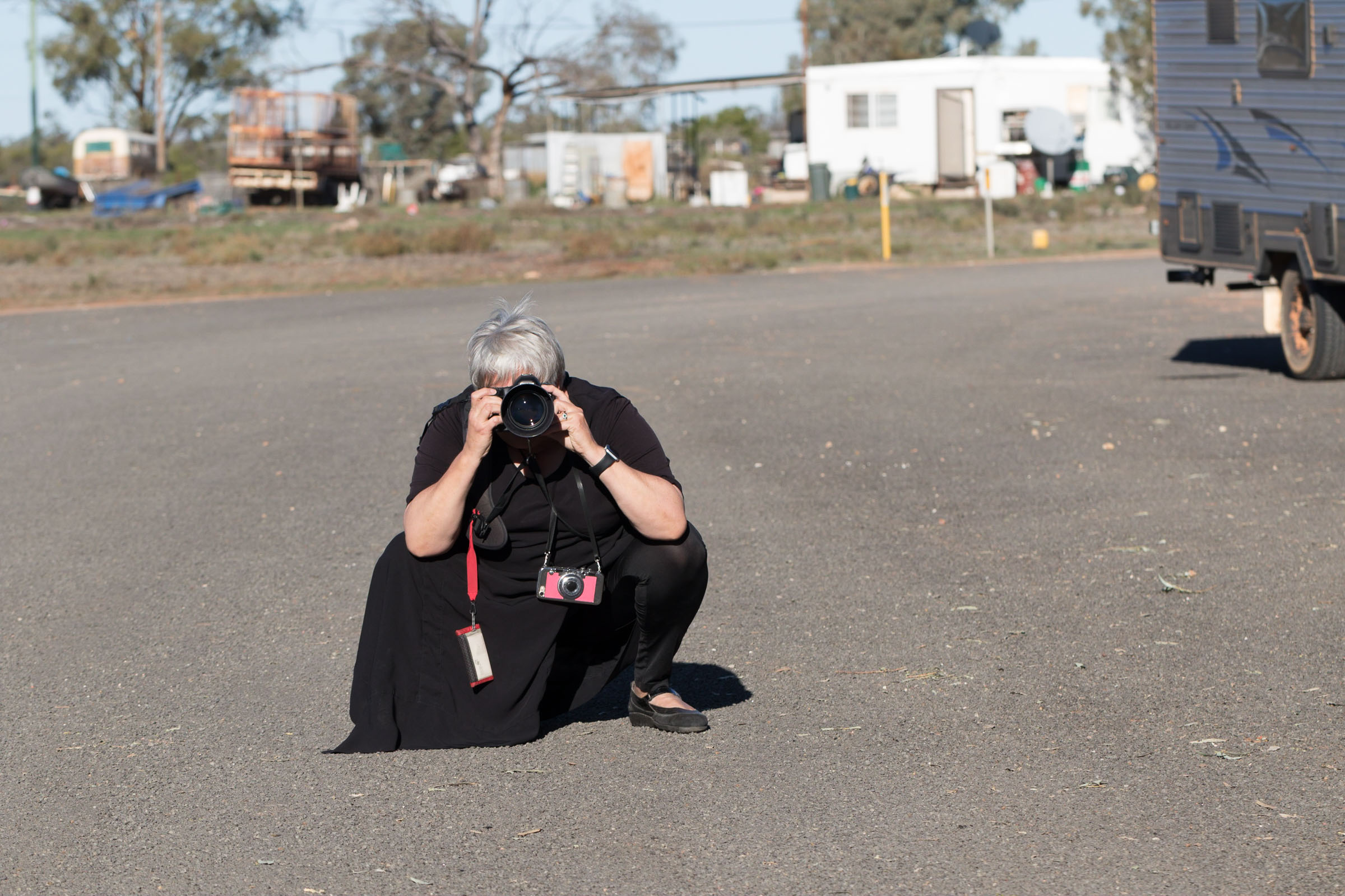 Photo of Caro Telfer, photographer, squatting i a not very ladylike position to take a photo.