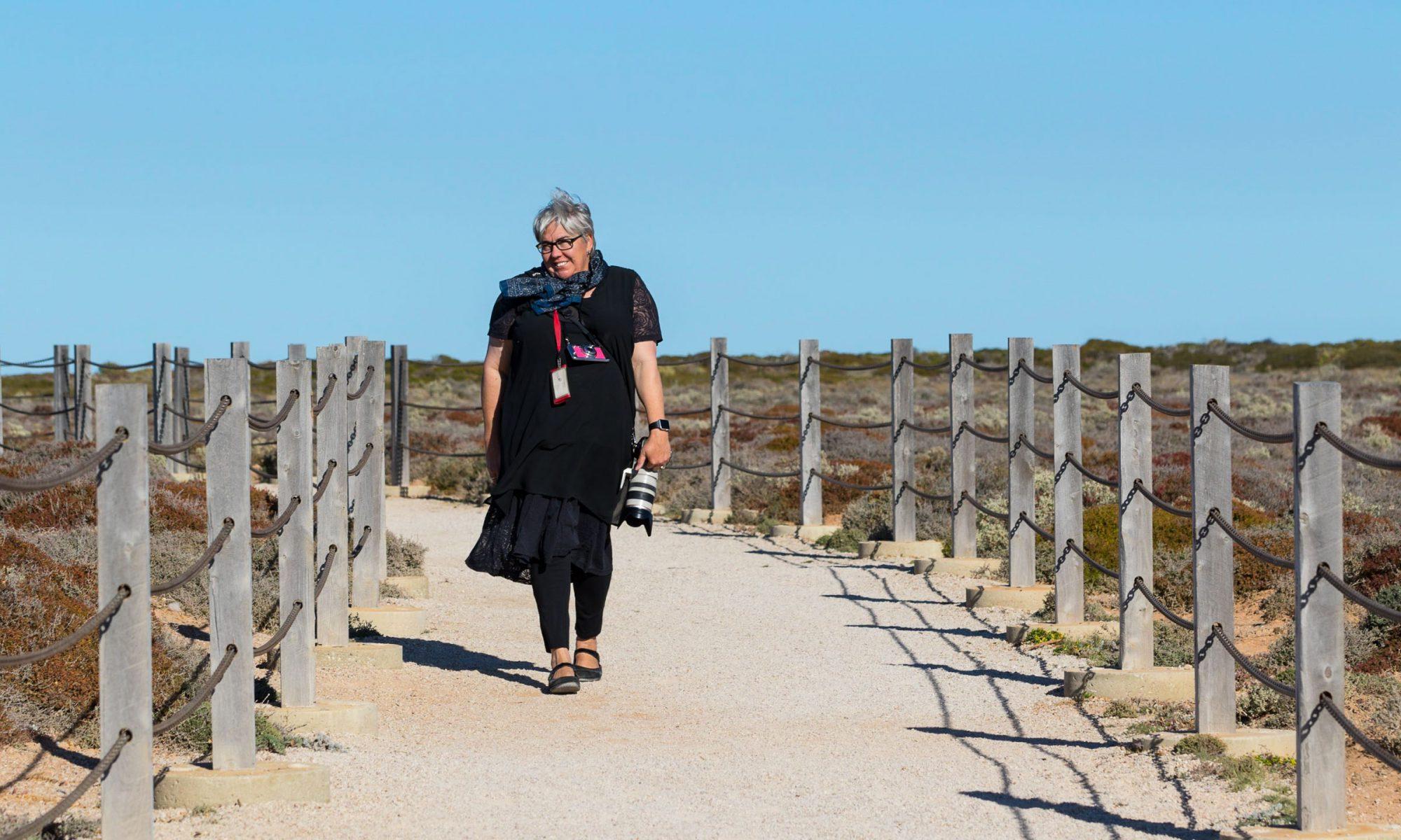 photo of Caro Telfer, carrying a camera on coastal path