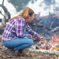 Photo of country girl toasting marshmallow on campfire