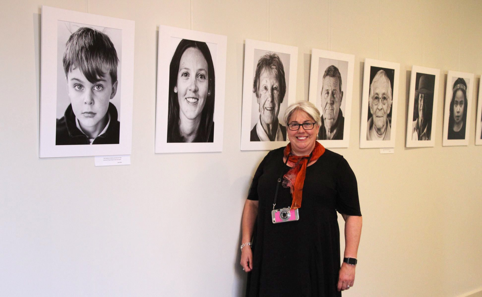 Caro Telfer standing in front of black and white portraits on a wall