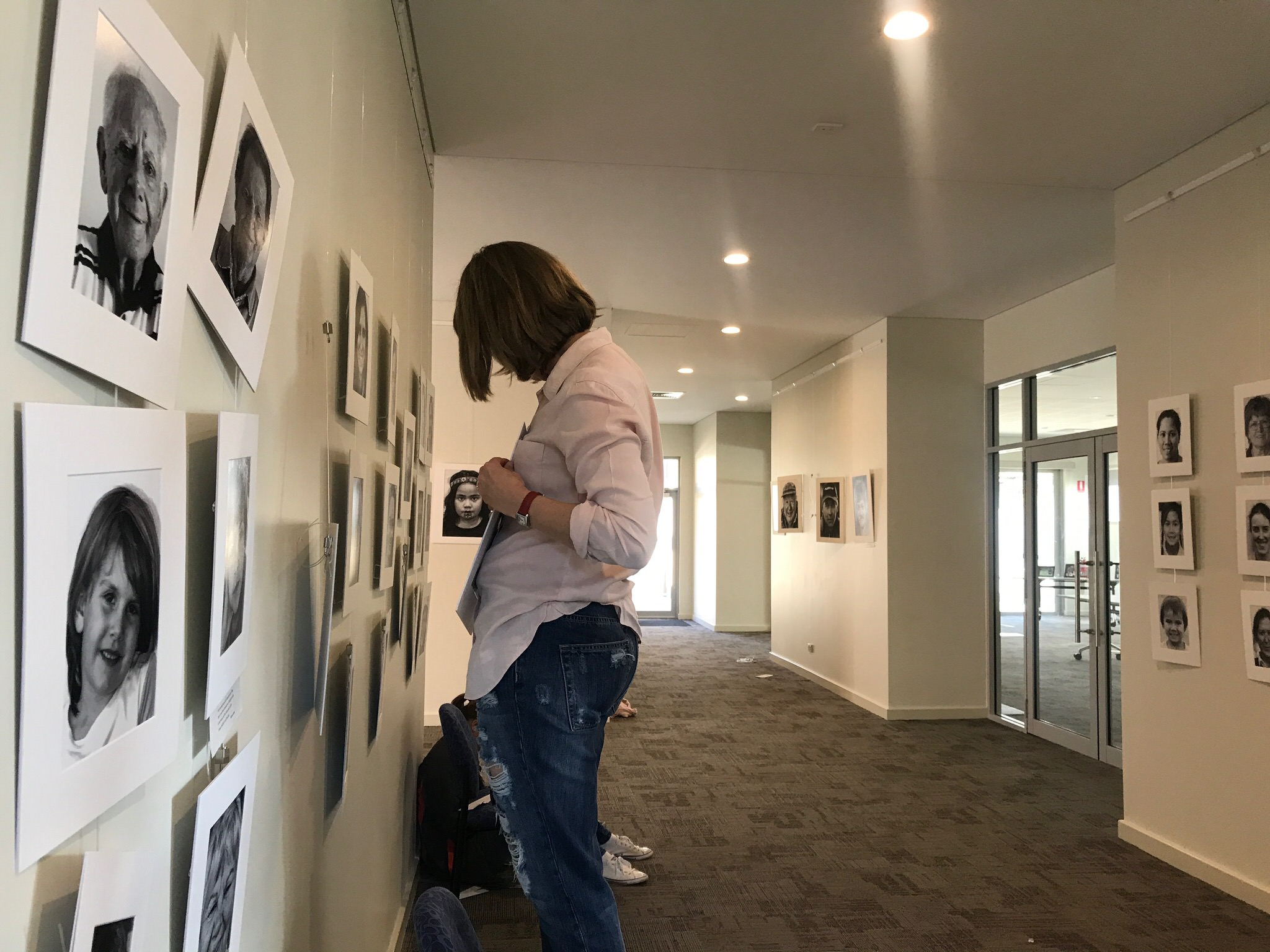 Photo of woman hanging photos in the exhibition