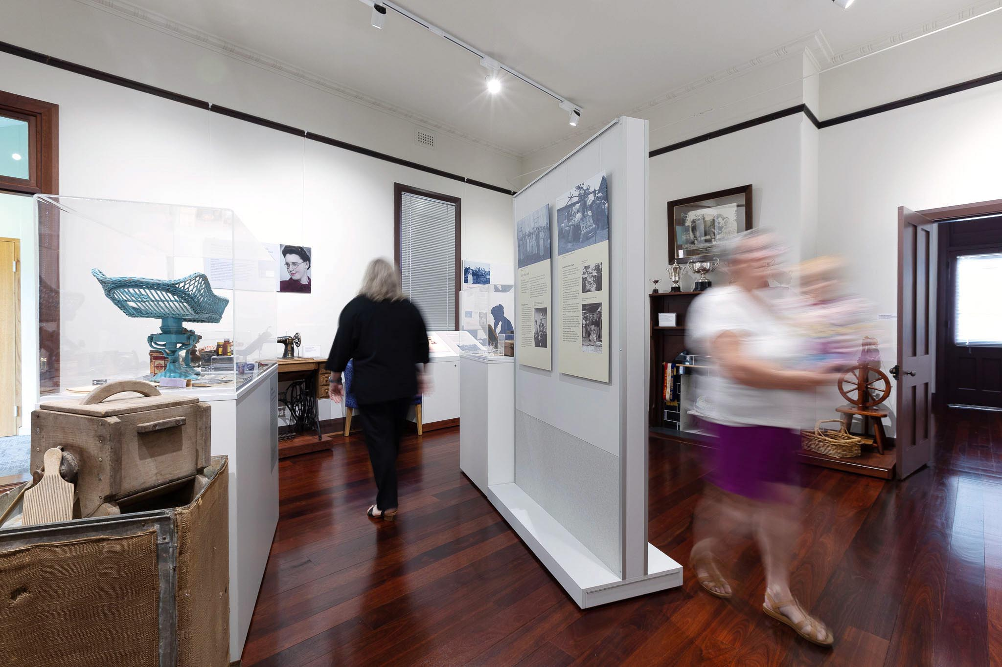 Wide angle view of main room of historical centre showing polished wood floor, museum displays, and people blurred moving through the scene.