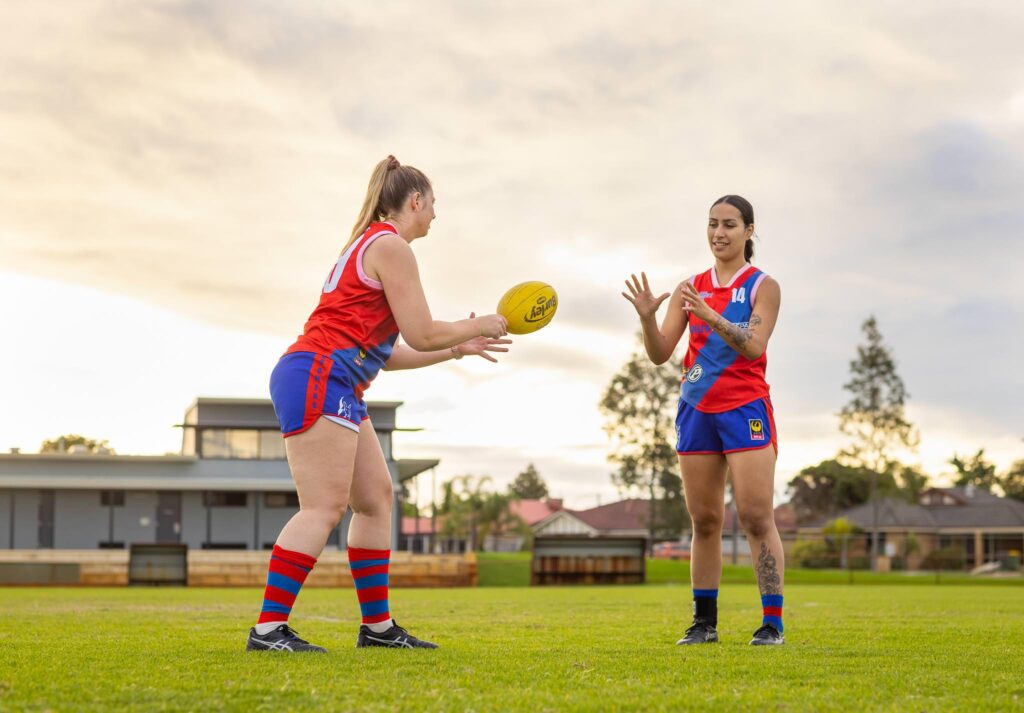Female teammates practise hand balling at Aussie Rules football training