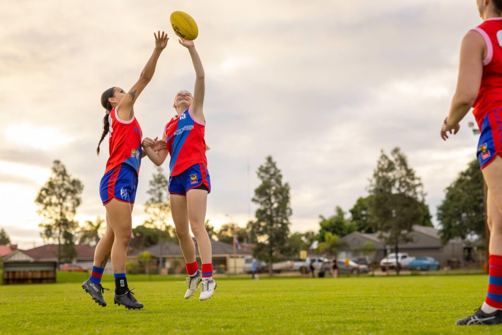 Two young women playing Aussie Rules football jump to tap the ball.