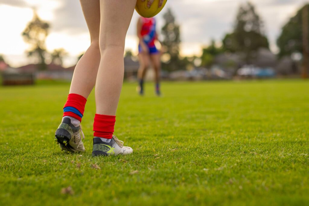 view from behind showing legs of female football player with socks and boots on green grass of oval