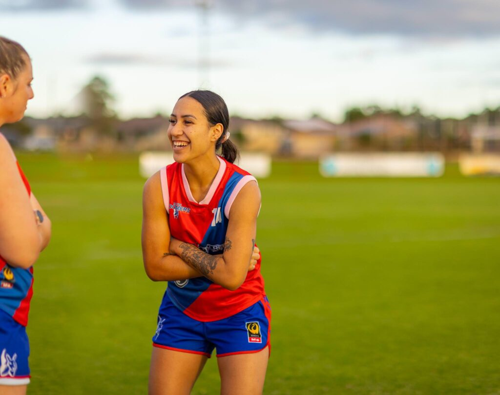 Woman football player with arms crossed laughing as she looks at another player