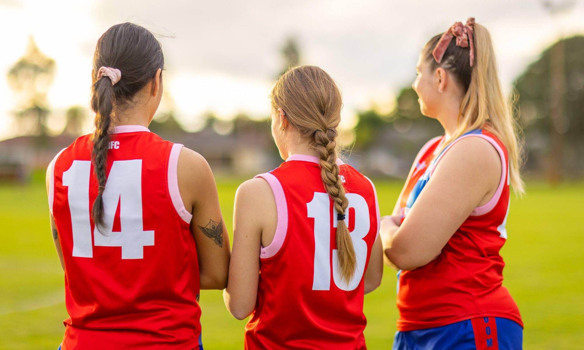 three young women wearing football jerseys seen from behind